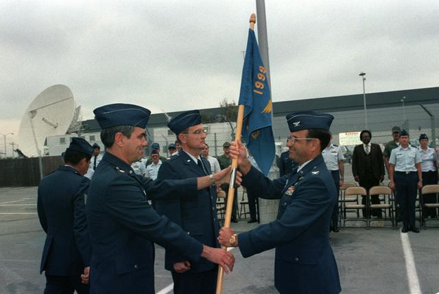 Major (MAJ) Alan K. Williams, commander, 1999th Communications Squadron, presents the squadron flag to Colonel (COL) Donald Hard, commander, Sunnyvale Satellite Control Facility, to pass on to Major (MAJ) Thomas L. Hickerson, new commander of the 1999th