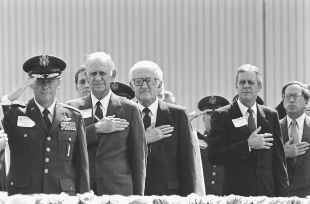 Distinguished guests honor the flag during the rollout ceremony for the first C-5B Galaxy aircraft at the Lockheed Aircraft Corp. From left to right are: General Thomas Ryan Jr., commander in chief, Military Airlift Command; Secretary of the Air Force Verne Orr; Senator Mack Mattingly, Republican-Georgia; and Georgia Governor Joe Frank Harris