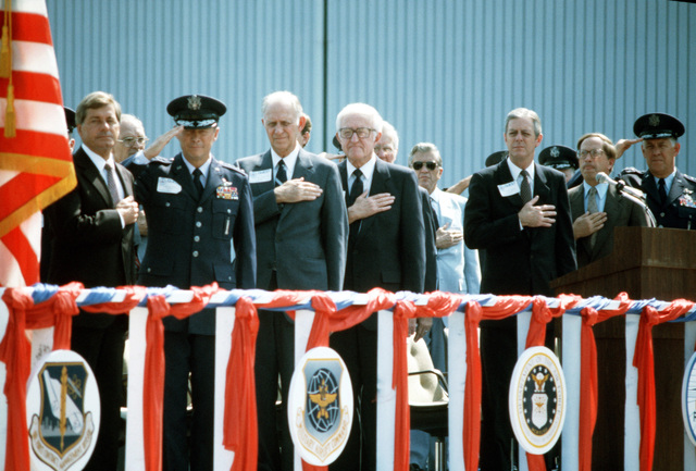 Distinguished guests pay respects to the flag during the rollout ceremony for the first C-5B Galaxy aircraft. Standing, left to right, are: Senator Mack Mattingly, Republican-Georgia; General Thomas M. Ryan Jr., commander in chief, Military Airlift Command; Secretary of the Air Force Verne Orr; Roy Anderson, chairman, Lockheed Aircraft Corp.; Georgia Governor Joe Frank Harris, Senator Sam Nunn, Democrat-Georgia; and General Lawrence Skantze, commander, Air Force Systems Command