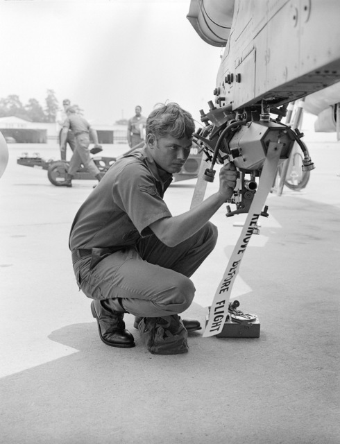 AIRMAN First Class (A1C) Mark Mathias, an aircraft armament systems specialist, prepares weapons station No. 2 of an aircraft for loading during gunnery meet GUNPOWDER 85