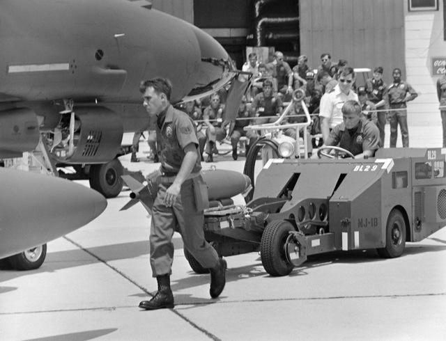 Munitions specialists use an MJ-1B bomb loader to load a bomb on an F-4E Phantom II aircraft during gunnery meet GUNPOWDER 85