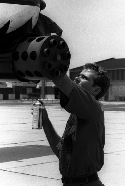 STAFF SGT. Tom M. Jones cleans the 30mm GAU-8A gun on an A-10A Thunderbolt II aircraft during the aerial gunnery competition Gunpowder '85