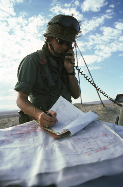 Captain (CPT) Mark Lee, an observer from 602nd Tactical Air Control Wing, uses the radio and checks his map while coordinating for the forward air controller and judges during the Air Warrior 85-12 exercise