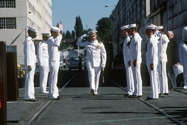 A US Navy commander salutes as he arrives for the recommissioning of the small repair ship USS SPHINX (ARL 24)