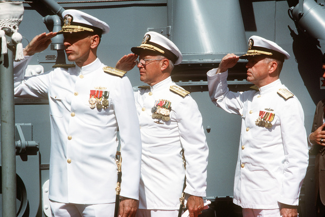 (Left to Right) Rear Admiral George W. Davis Jr., commander, Naval Surface Force, US Pacific Fleet; Rear Admiral Laverne S. Severance, commander, Naval Base, Seattle, and Commodore David F. Chandler, deputy commander, Naval Surface Force, US Atlantic Fleet, salute the flag during the commissioning ceremony for the guided missile frigate USS CARR (FFG 52)