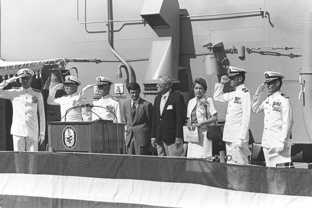 Officers salute during the commissioning ceremony for the guided missile frigate USS CARR (FFG 52). (Left to right) Rear Admiral G. Davis Jr., commander Naval Surface Force, US Pacific Fleet; Rear Admiral Laverne Severance, commander, Naval Base, Seattle; Commodore D. Chandler, deputy commander, Naval Surface Force, US Atlantic Fleet; J. Gilbride Jr., Mr. J. Yusen, Mrs. G. Carr Bensilhe, sponsor; Captain J. Brennan, Chaplain Corps, Naval Base, Seattle, and Commander Robert J. Horne, commanding officer, USS CARR
