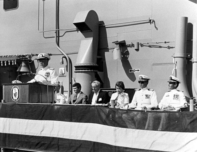 "Rear Adm. Laverne S. Severance Jr., commander, Naval Base, Seattle, addresses guests at the commissioning of the guided missile frigate USS CARR (FFG-52). Other dignitaries attending are, from the left: Commodore David F. Chandler, deputy commander, Naval Surface Force; John T. Gilbride Jr., Todd Seattle; Jack Yusen, ""SAMUEL B. ROBERTS"" Survivors Association; Sponsor Goldie Carr Bensilhe; Capt. J. F. Brennan, chaplain, Naval Base, Seattle; and Cmdr. R. J. Horne, commanding officer"