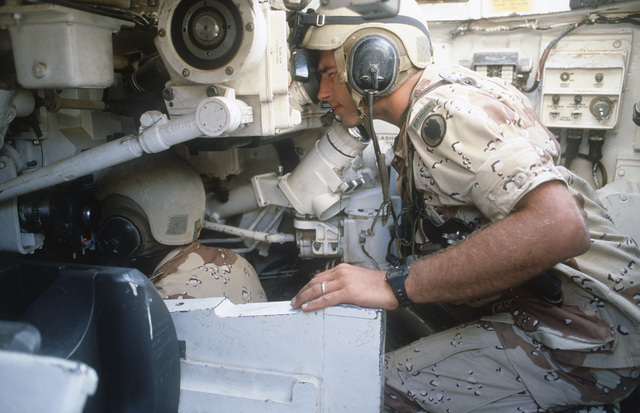 A 2nd Battalion, 70th Armor, 24th Infantry Division, tank driver operates an M-60 main battle tank as the commander, seated above and behind, looks out of a periscope during the multinational joint service Exercise BRIGHT STAR '85