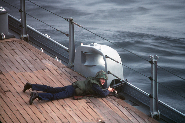 A crew member aboard the battleship USS IOWA (BB 61), armed with a M79 40 mm grenade launcher and an M14 rifle, participates in a self defense force test during Exercise OCEAN SAFARI '85