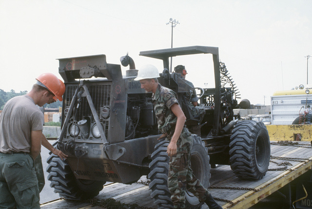 A fork lift is unloaded from a flatbed truck at the Wilmington Port Authority prior to being loaded aboard a ship for transport to the multinational joint service Exercise BRIGHT STAR '85