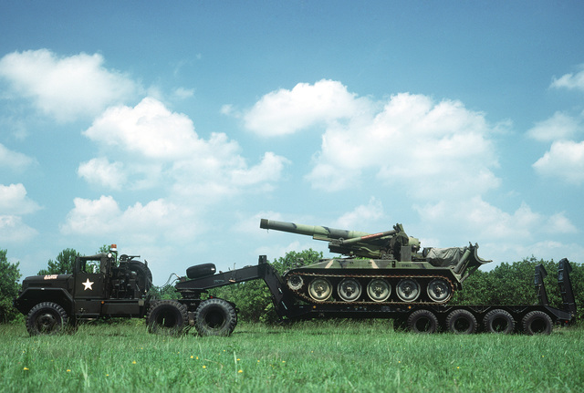 A left side view of an M123A1C 10-ton tractor truck and M747 semi-trailer loaded with an M110 203 mm self-propelled Howitzer