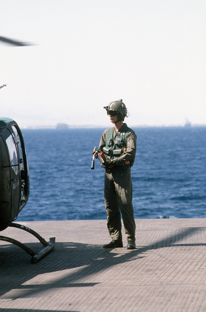 A pilot checks a fire extinguisher before flying a helicopter that has just been off-loaded from a ship for use during the multinational joint service Exercise BRIGHT STAR '85