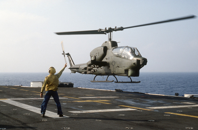 A plane director aboard the amphibious assault ship USS IWO JIMA (LPH 2) signals to an AH-1T Sea Cobra helicopter during the multinational joint service Exercise BRIGHT STAR '85