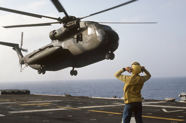 A plane director aboard the amphibious assault ship USS IWO JIMA (LPH 2) signals to an CH-53 Sea Stallion helicopter during the multinational joint service Exercise BRIGHT STAR '85