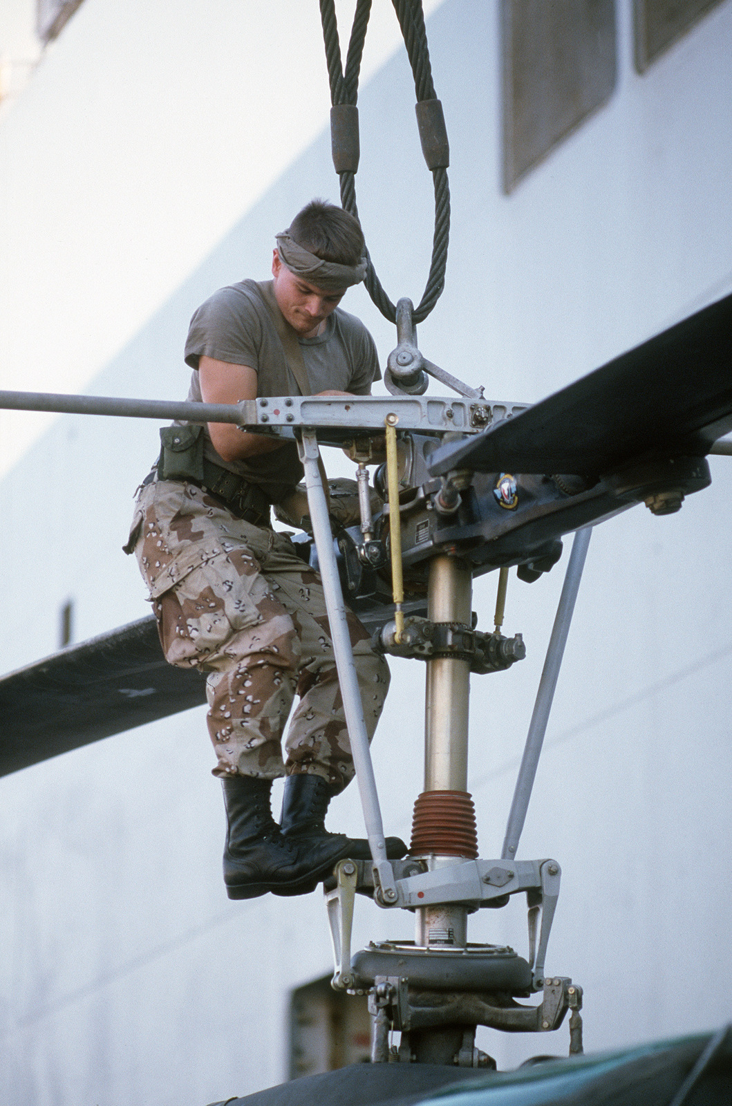 a technician checks the rotor on a helicopter that has jsut been off