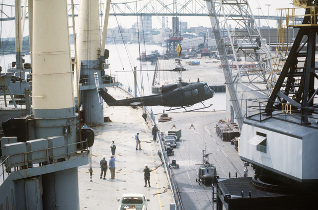 A UH-1 Iroquois helicopter is loaded onto the vehicle cargo ship SS ADMIRAL WILLIAM M. CALLAGHAN (T-AKR 1001) for transport to the multinational joint service Exercise Bright Star '85