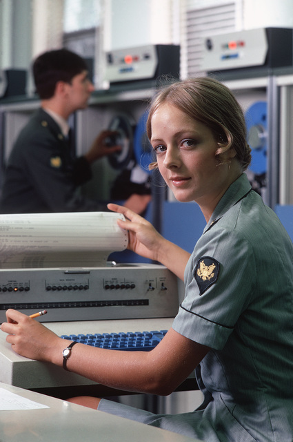 A US Army specialist 4 examines a computer printout