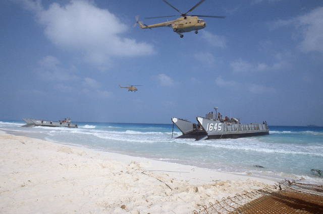 A Utility Landing Craft (LCU 1645) and an Mechanized Landing Craft (LCM8) land on the coast during the multinational joint service Exercise BRIGHT STAR '85. Overhead are two Soviet-made Mi-8 Hip Helicopters