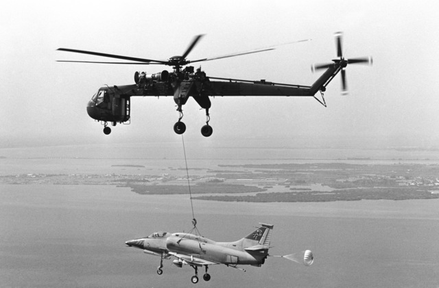 An air-to-air left side view of a CH-54 Skyhook helicopter of the 2348th Transportation Co., Mississippi Nationa Guard, transporting a damaged Marine Corps A-4 Skyhawk aircraft to Naval Air Station, Pensacola, Florida, from Patrick Air Force Base, Florida. The aircraft was struck by lighting while parked on the flight line