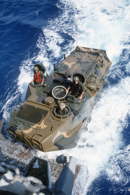 An LVTP7 tracked landing vehicle climbs the stern ramp of the tank landing ship USS LA MOURE COUNTY (LST 1194) during the multinational joint service Exercise BRIGHT STAR '85