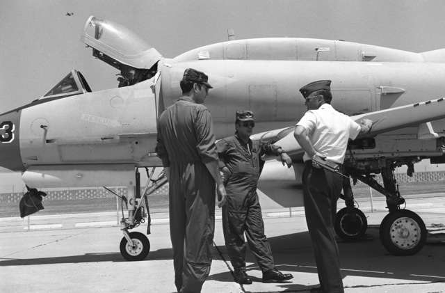 Captain (CPT) James N. Miller, left, and CHIEF Warrant Officer Eric D. Dauphine, center, both of the 2348th Transportation Co., Mississippi National Guard, discuss the airlift operation of a damaged Marine Corps A-4 Skyhawk aircraft with Major (MAJ) Jack G. Merrell Jr., airfield manager and chief of base operations. The aircraft was struck by lighting while parked on the flight line