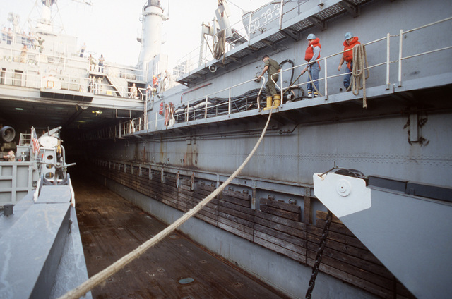 Crew members handle landing craft mooring lines in the docking well of the dock landing ship USS PENSACOLA (LSD 38) during the multinational joint service Exercise BRIGHT STAR '85