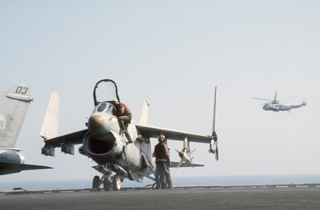 Crewmen service an A-7E Corsair II aircraft parked on the nuclear-powered aircraft carrier USS NIMITZ (CVN 68) during the multinational joint service Exercise BRIGHT STAR '85