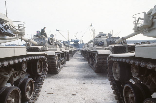 M-60 main battle tanks are staged on the dock prior to being loaded aboard the vehicle cargo ship SS ADMIRAL WILLIAM M. CALLAGHAN for transport to the multinational joint service Exercise BRIGHT STAR '85 in Egypt