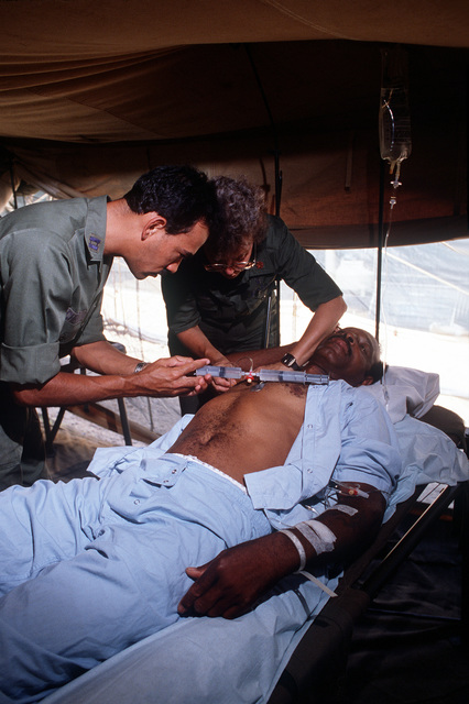 MAJ. Angela Watwood, anesthesiologist, and CAPT. Cedric Chenet, dentist, do an auxiliary nerve block on a patient in the 363rd Tactical Hospital during the multinational joint service exercise Bright Star '85