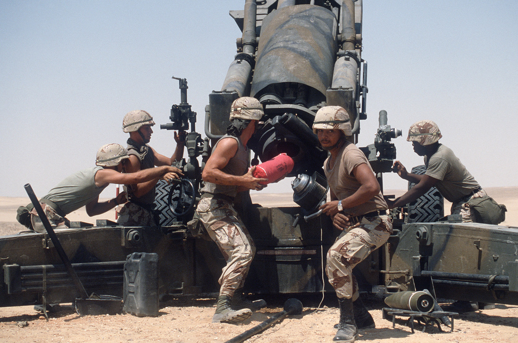 Members of the 3rd Field Artillery load a powder charge into an M-198 155mm howitzer while participating in a live fire exercise during the multinational joint service Exercise BRIGHT STAR '85