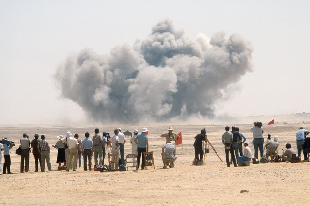 Observers attending a combined arms live fire demonstration watch explosions on the firing range during the multinational joint service Exercise BRIGHT STAR '85