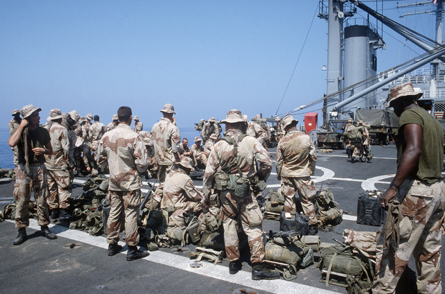 U.S. Marines aboard the tank landing ship USS LA MOURE COUNTY (LST 1194) stand by with their gear after returning from an exercise in the Egyptian desert during the multinational joint service Exercise BRIGHT STAR '85
