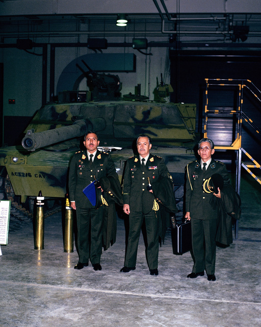 Members of a Peruvian military delegation visiting the US Army Armor Center gather for a photograph in front of an M1 Abrams main battle tank