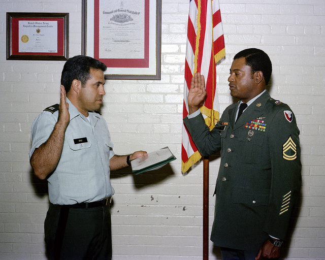 Sergeant First Class (SFC) Marshall Wright Jr. is sworn in for a four-year re-enlistment by Captain (CPT) Louis D. Cruz, a unit commander at Rock Island Arsenal
