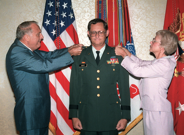 John O. Marsh Jr., Secretary of the Army, promotes COL William A. Stofft, CHIEF of Military History, to the rank of brigadier general during a ceremony at the Fort Myer Officers Club. Assisting Marsh is Stofft's wife, Patty