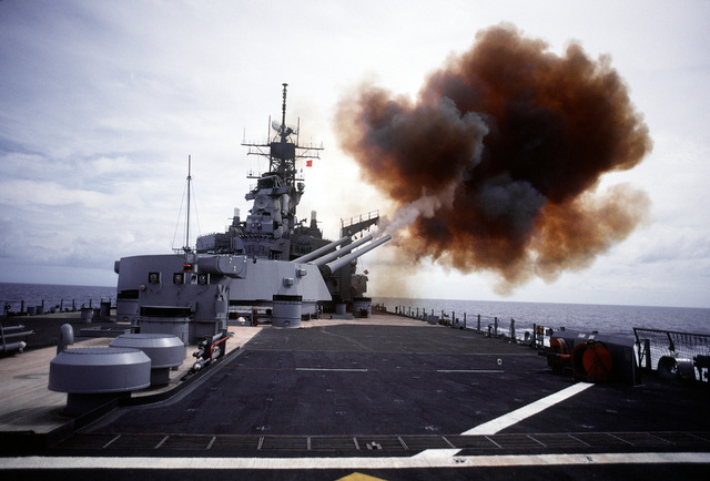 A salvo is fired from the No. 3 Mark 7 16-inch/50 caliber gun turret aboard the battleship USS IOWA (BB-61). The turret is trained as far forward as possible on the starboard side with guns elevated to the level of the BGM-109 Tomahawk missile armored box launchers. The guns are being fired in order to determine the launcher`s overpressure resistance.Third view in a series of five