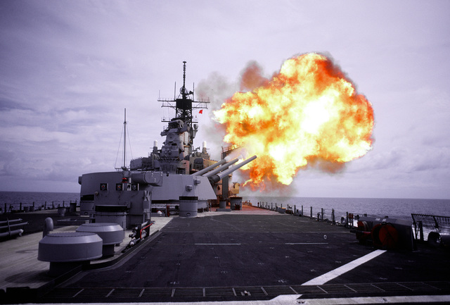 A salvo is fired from the No. 3 Mark 7 16-inch/50 caliber gun turret aboard the battleship USS IOWA (BB-61). The turret is trained as far forward as possible on the starboard side with guns elevated to the level of the BGM-109 Tomahawk missile armored box launchers. The guns are being fired in order to determine the launcher`s overpressure resistance.Fifth view in a series of five