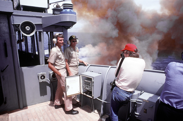 """Dallas """"Morning News"""" photographer William Snyder takes an informal photo of CAPT. John J. Chernesky left, exectuive officer of the battleship USS IOWA (BB-61), and CAPT. Gerald E. Gneckow, commanding officer, using a single gun salvo from turret No. 2 as a backdrop"""