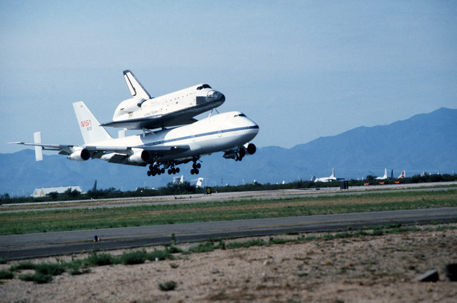 A NASA Boeing 747 carrier aircraft transporting the space shuttle orbiter Challenger approaches for a landing at the base for refueling. The shuttle is en route to Cape Canaveral, Florida