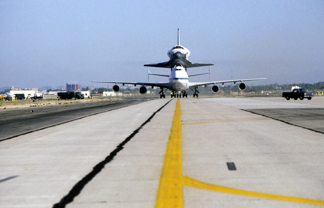 A NASA Boeing 747 carrier aircraft transporting the space shuttle orbiter Challenger taxis on the runway after landing at the base for refueling. The shuttle is en route to Cape Canaveral, Florida