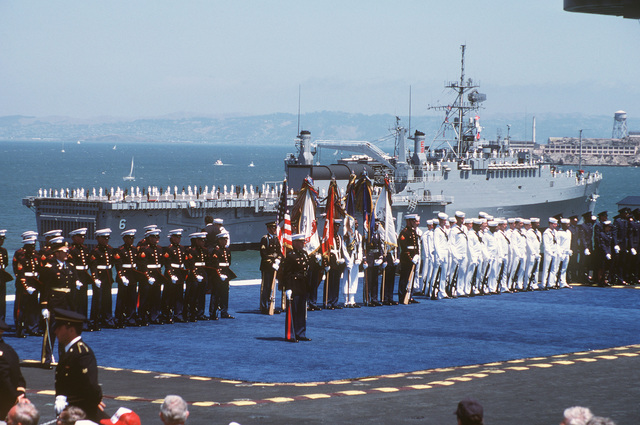A joint services honor guard participates in the Peace in the Pacific celebration commemorating the 40th anniversary of the end of the war with Japan, aboard the nuclear-powered aircraft carrier USS ENTERPRISE (CVN 65). Passing in review in the background is the amphibious transport dock USS DULUTH (LPD 6)