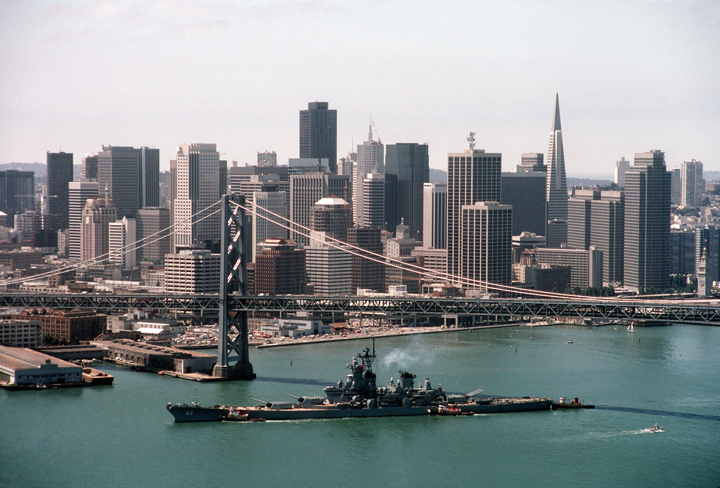 Aerial port beam view of the battleship USS NEW JERSEY (BB 62) passing beneath the San Francisco Bay Bridge with the San Francisco in the background. The NEW JERSEY is participating in the Peace in the Pacific celebration, commemorating the 40th anniversary of the end of the war with Japan