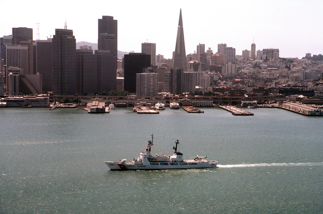 Aerial port beam view of the high endurance cutter USCGC MIDGETT (WHEC 726) underway during the Peace in the Pacific celebration commemorating the 40th anniversary of the end of the war with Japan. The San Francisco skyline is in the background