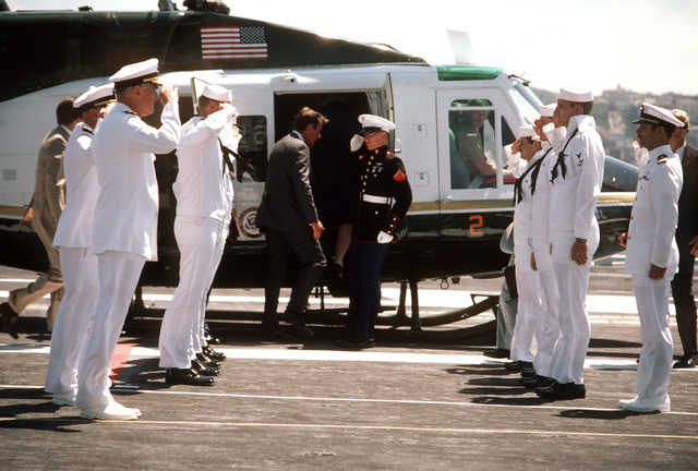 Members of an honor cordon salute as Vice President George Bush prepares to board a UH-1N Iroquois helicopter aboard the nuclear-powered aircraft carrier USS ENTERPRISE (CVN 65). Vice President Bush spoke during the Peace in the Pacific celebration commemorating the 40th anniversary of the end of the war with Japan