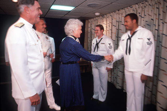 Mrs. George Bush and Admiral James D. Watkins (left), chief of Naval Operations, congratulate newly reenlisted sailors aboard the nuclear-powered aircraft carrier USS ENTERPRISE (CVN 65). The crewmen were reenlisted by Vice President Bush following the Peace in the Pacific celebration commemorating the 40th anniversary of the end of the war with Japan