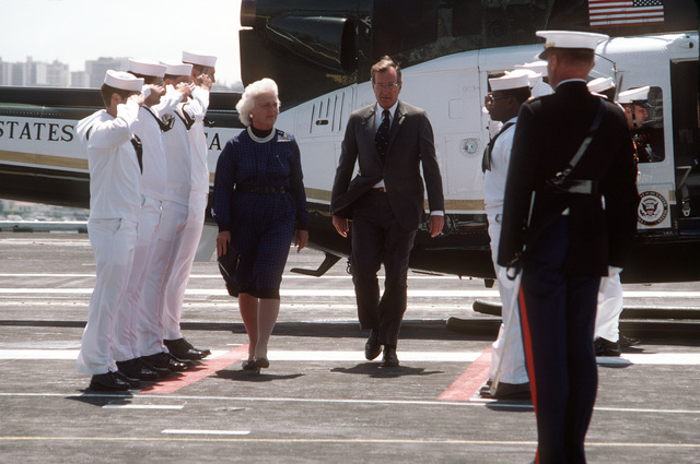 Vice President and Mrs. George Bush walk between a Navy honor cordon as they arrive aboard the nuclear-powered aircraft carrier USS ENTERPRISE (CVN 65) for the Peace in the Pacific celebration commemorating the 40th anniversary of the end of the war with Japan. Behind them is the UH-1N Iroquois helicopter that transported them to the ship