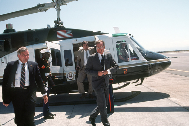 Vice President George Bush (right) gets off a UH-1N Iroquois helicopter. Vice President Bush is en route to the Peace in the Pacific celebration, commemorating the 40th anniversary of the end of the war with Japan. The celebration is being held aboard the nuclear-powered aircraft carrier USS ENTERPRISE (CVN 65)
