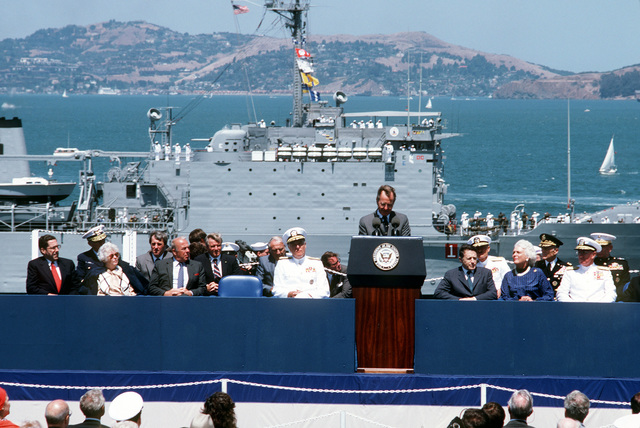 Vice President George Bush speaks aboard the nuclear-powered aircraft carrier USS ENTERPRISE (CVN 65) during the Peace in the Pacific celebration commemorating the 40th anniversary of the end of the war with Japan. Secretary of Defense Caspar Weinberger and Mrs. George Bush are seated to the right of the podium and Admiral James D. Watkins, chief of naval Operations, is seated to the left. Passing in review in the background is the tank landing ship USS FREDERICK (LST 1184)