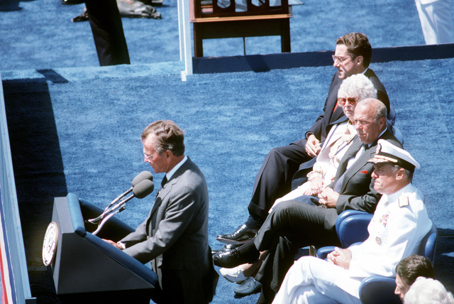Vice President George Bush speaks aboard the nuclear-powered aircraft carrier USS ENTERPRISE (CVN 65) during the Peace in the Pacific celebration commemorating the 40th anniversary of the end of the war with Japan. Seated behind him is Admiral James D. Watkins (foreground), chief of Naval Operations