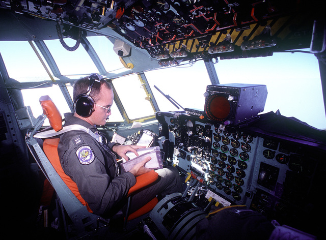 CAPT. Erdie O. Lansford II of the 37th Tactical Airlift Squadron checks his manifest while piloting a C-130E Hercules on a container delivery system (CDS) airdrop during a training exercise